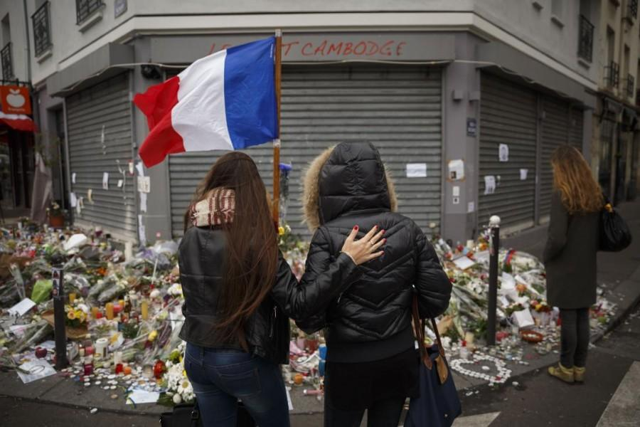 Two women mourn the victims of the recent terror attacks outside of the Petit Cambodge