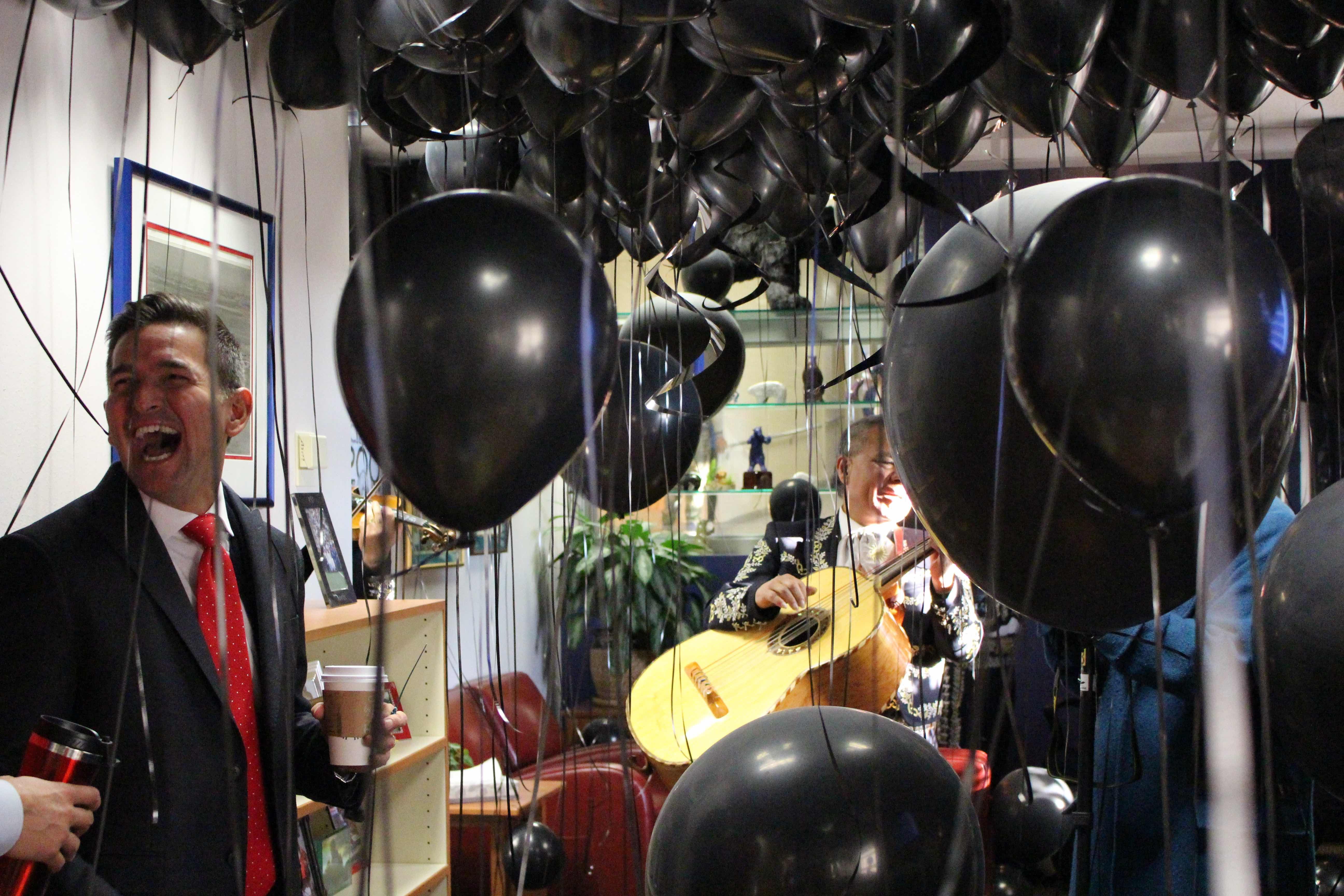 Principal Silva is surprised in his office by balloons and a mariachi band.