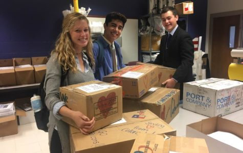 Junior Brooke Schmidt, Senior Max Gomez, and Sophomore Taid Zdinak finish packing boxes of supplies to send to students affected by Hurricane Harvey in Houston.