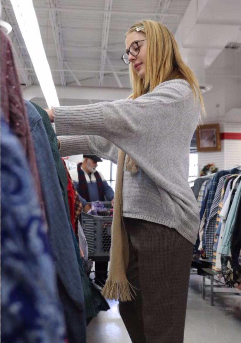STYLES: Senior Emma Stengel looks through jackets at Arc Thrift store. Stengel prefers thrift stores because she is able to find clothing that is affordable, unique, and environmentally friendly.