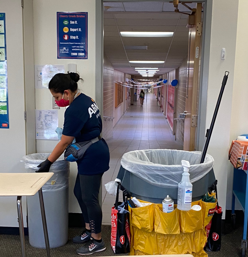 MAINTAINING COVID PRECAUTIONS: ABM worker Araseli works to clean the school after hours. The custodians must go up and down each row of desks, spraying and wiping them down, in addition to their usual jobs.
