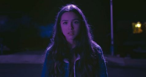 "A scene from the ""Drivers License"" music video, which features 17-year-old Olivia Rodrigo walking and driving through the suburbs. Rodrigo"