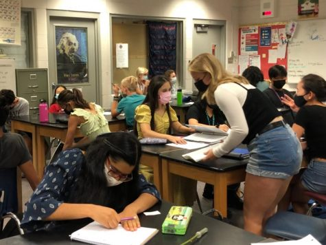 Students learn while masked in a science classroom at Creek.