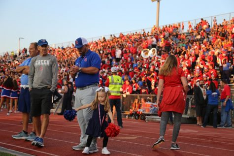 """Mackenzie Wilkins, daughter of Creek athletic director Jason Wilkins, dances with blue and red pom-poms in her hands and bows in her hair on the sideline during Creek's 31-0 victory over Pomona at Stutler on Fri. Sep. 3. """"She was there to spend time with me,"""" Wilkins said. """"She loves to dance and loves to cheer 'Let's Go Cherry Creek!'"""""""