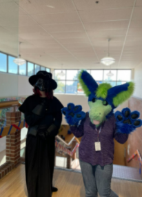 """On Mon Oct 4, students dressed as their favorite movie character. Freshman Paige Mack (left) is dressed in her outlandish outfit based on the movie and video game character SCP-049; sophomore Annie Bellini (right) is dressed in her handmade fursuit based on her own original character. The friends relax at the library after a long day of posing for pictures. """"Lots of people wanted photos, its fun,"""" Bellini said. """"I was just really excited for everything [spirit week], since I got to dress up and be myself."""""""